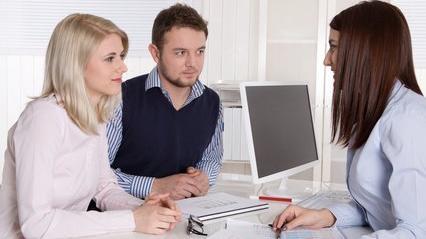 Un couple et une conseillère commerciale dans une banque
