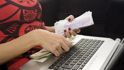 Une femme tenant des billets sur un ordinateur