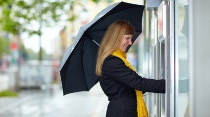 Femme devant un distributeur de billets de banque