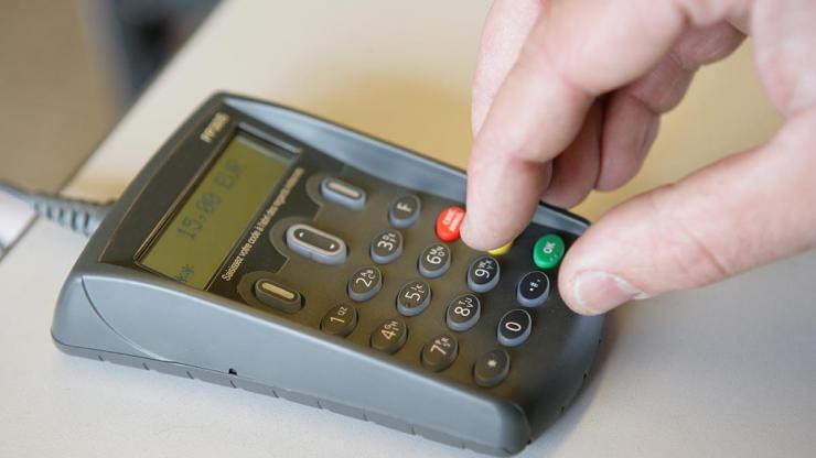 Personne entrant son code de carte bancaire sur un terminal de paiement électronique