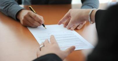 Une personne indiquant où signer un contrat