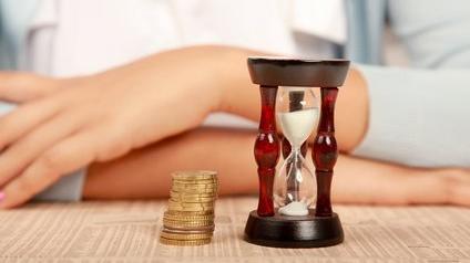 Un sablier et des pièces en euros