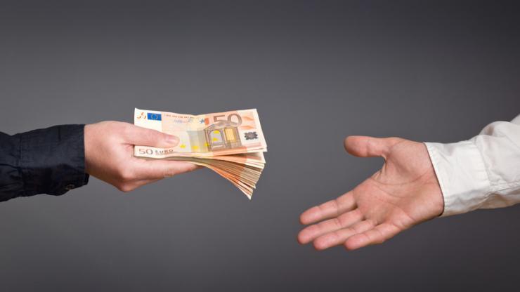 Une personne donnant des billets à une autre personne