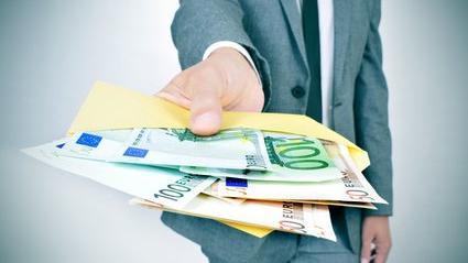 Un homme tendant des billets dans une enveloppe