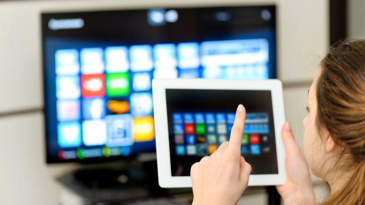 Une femme consultant sa tablette devant la télévision
