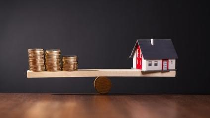 Maison et argent sur une balance