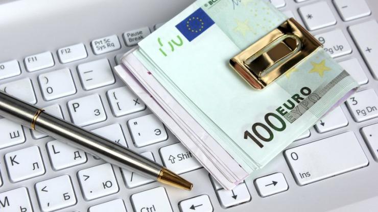 Un crayon et des billets sur un clavier