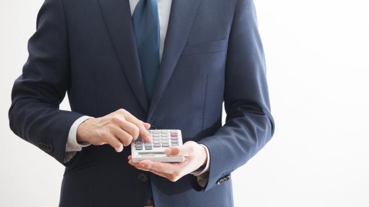 Homme en costume tenant une calculatrice