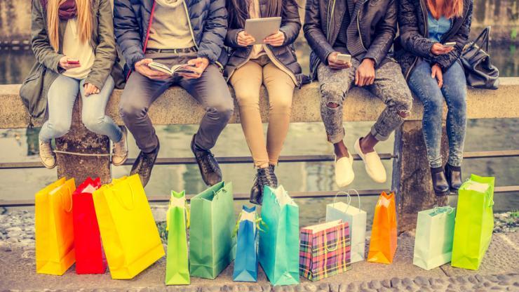Jeunes gens sur une rembarde avec des paquets devant eux