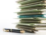 Un stylo à côté d'une pile de dossiers