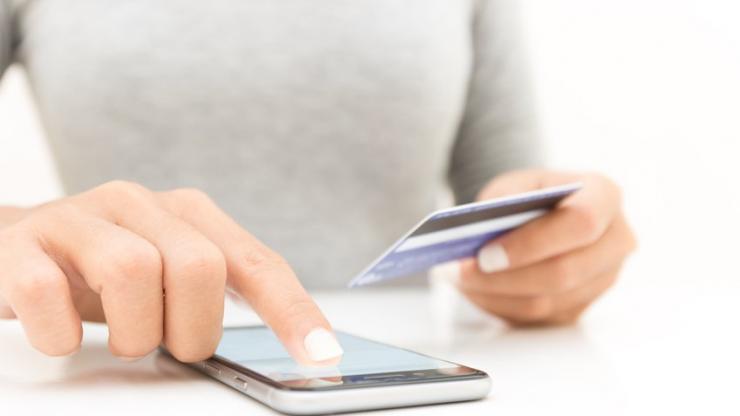 Gros plan de femme utilisant un smartphone et une carte bancaire