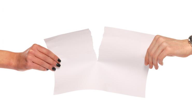 Un homme et une femme se dispute une feuille de papier déchirée