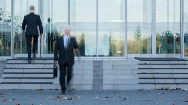 businessmen sortant et entrant dans un bâtiment