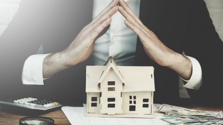 Homme joignant les mains au dessus d'une maquette de maison