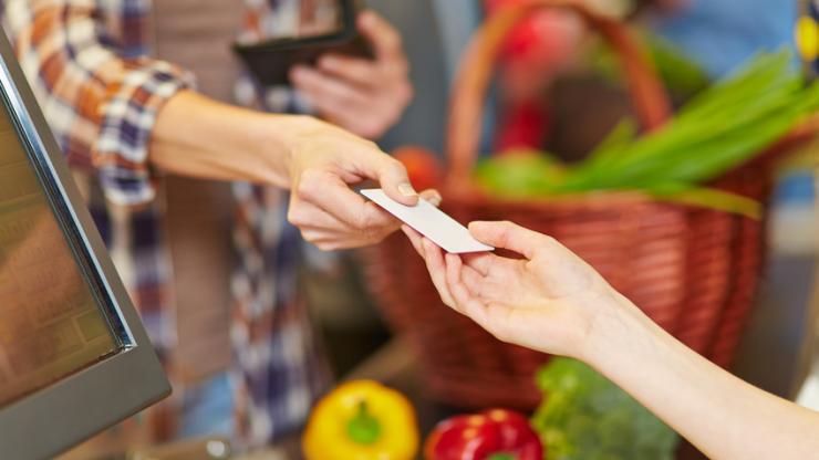 Femme présentant sa carte bancaire à la caisse d'un supermarché