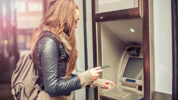 Jeune femme retirant de l'argent à un distributeur
