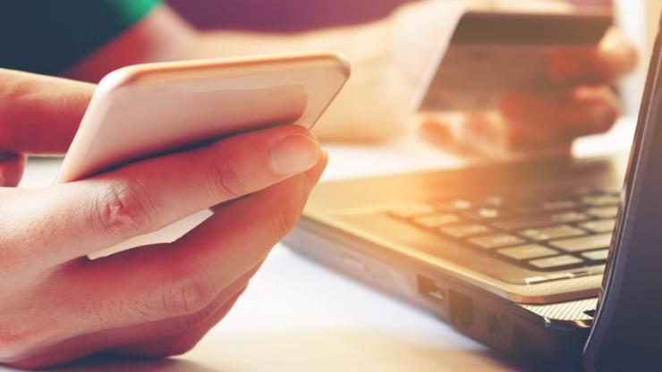 Homme tenant un smartphone et une carte bancaire devant un ordinateur
