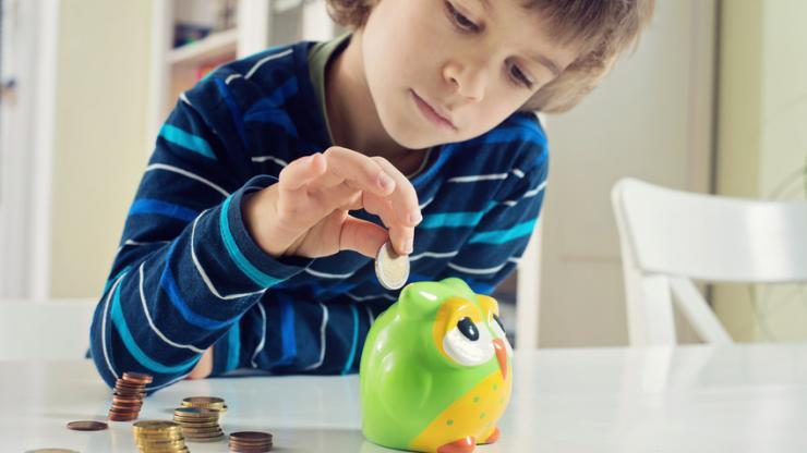 Enfant mettant des pièces dans une tirelire