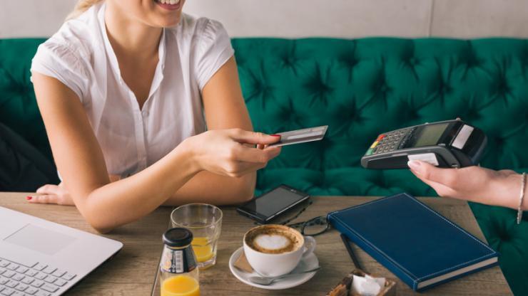 Femme payant par carte bancaire dans un café