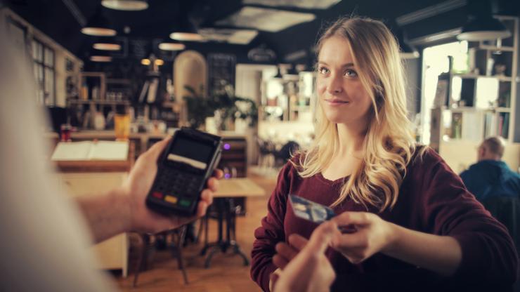 Jeune femme réglant un achat par carte bancaire