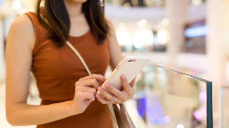 Femme utilisant un smartphone dans une galerie marchande