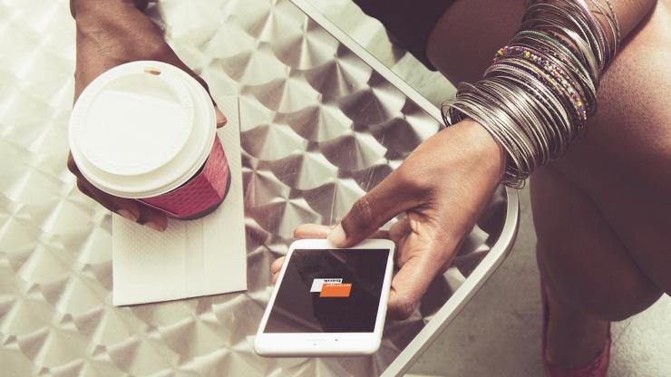 Un femme utilise l'application Orange Bank dans un café