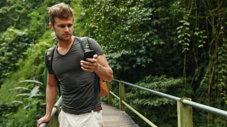 Homme utilisant son mobile lors d'une balade en forêt