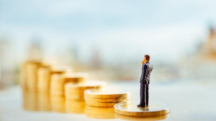 Miniature d'un homme se tenant sur une pile de pièces avec la ville en arrière-plan