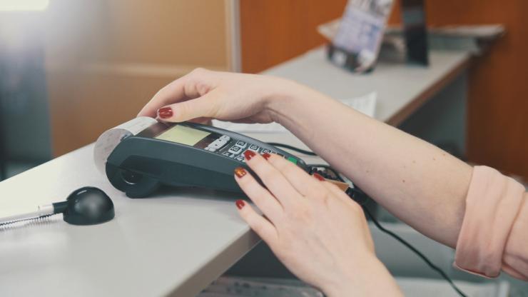 Femme effectuant un paiement par carte bancaire sur un terminal de paiement