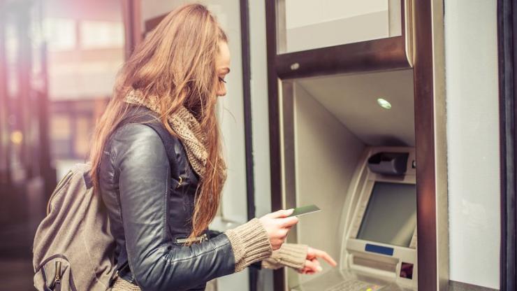 Jeune femme retirant de l'argent à un DAB