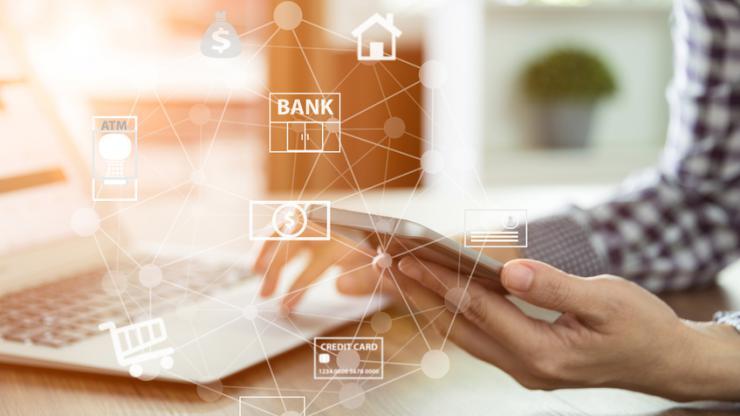 Homme consultant sa banque sur mobile et ordinateur