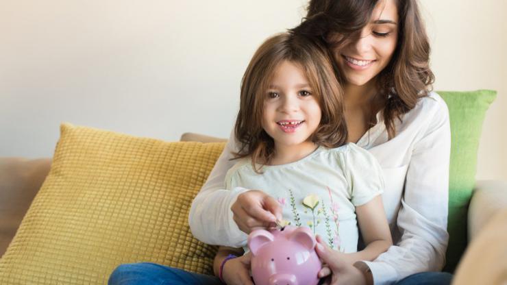Mère et fille mettant de l'argent dans une tirelire