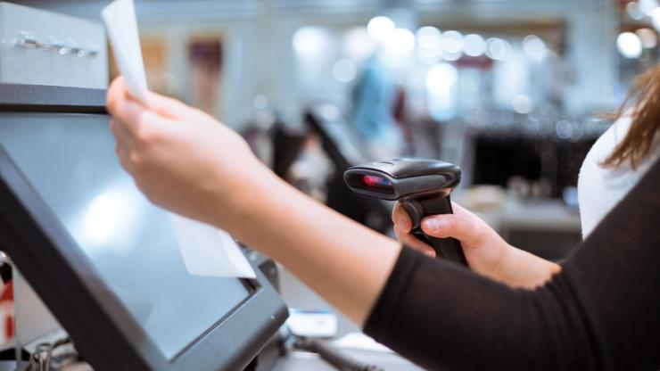 Femme scannant un article à un caisse automatique