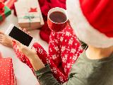 Jeune femme en bonnet de Noël consultant son smarphone