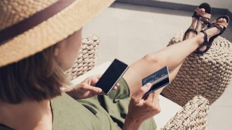 Jeune femme en vacances utilisant sa carte bancaire et son mobile
