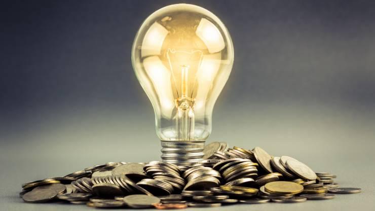 Ampoule allumée sur une pile de pièces