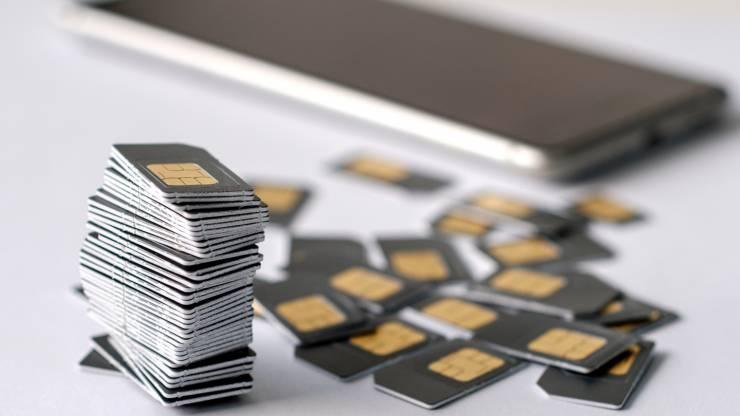 Pile de cartes SIM avec smartphone en arrière-plan