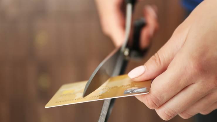 Mains coupant une carte bancaire avec une paire de ciseaux