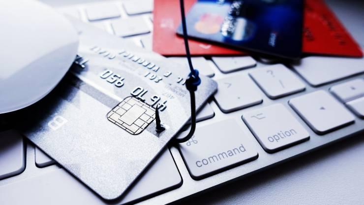 Carte bancaire hameçonné posé sur un clavier d'ordinateur