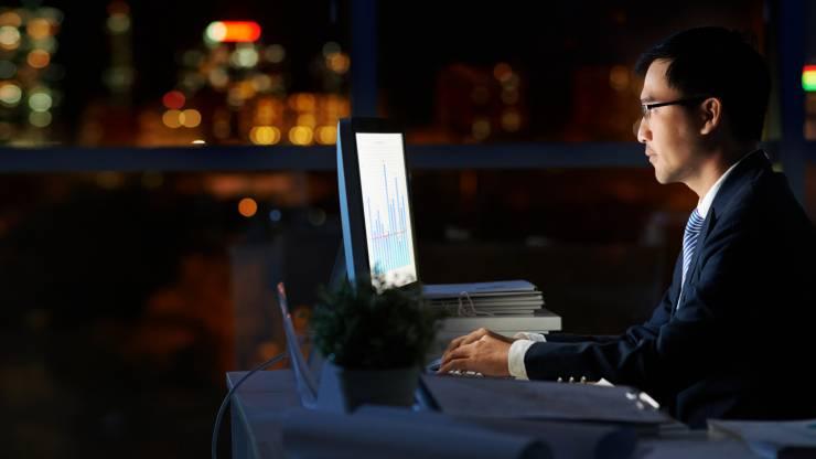 Homme en costume dans l'obscurité devant un écran d'ordinateur