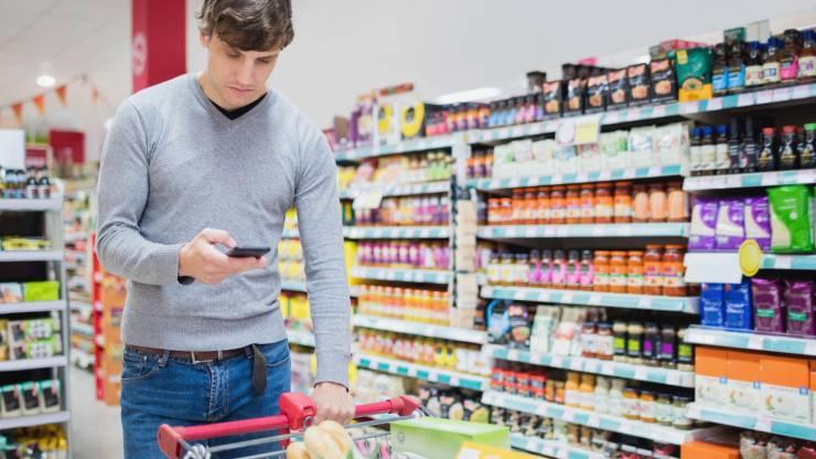 Homme consultant son smartphone en faisant ses courses