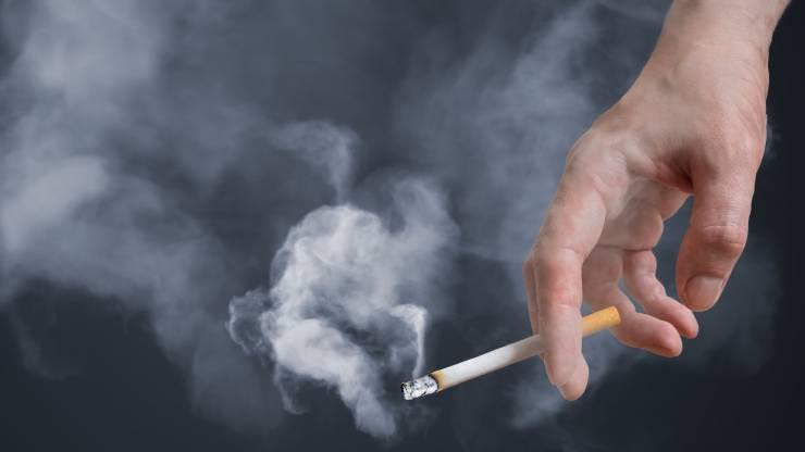 Main d'un homme tenant une cigarette allumée