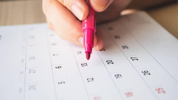 Main avec stylo écrivant sur un calendrier