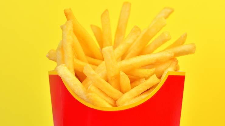 Cornet de frites rouge sur fond jaune