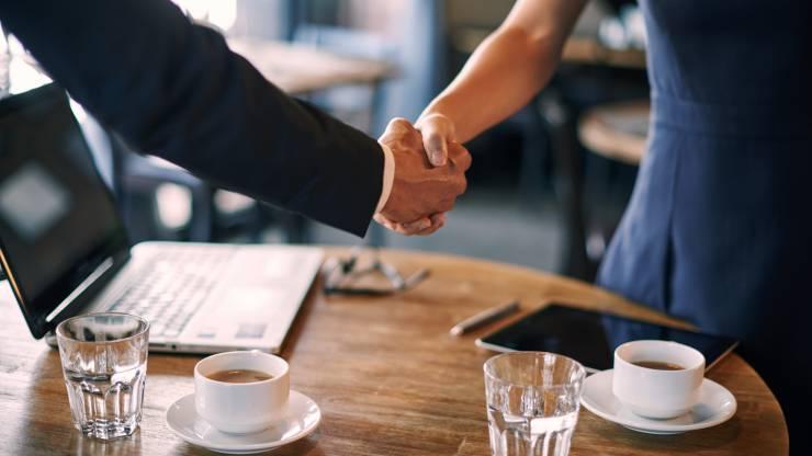 Poignée de main entre un homme et une femme dans un café