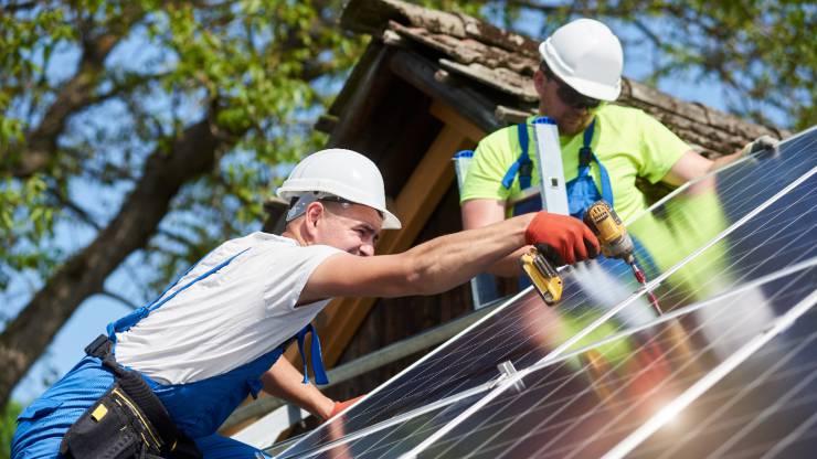 hommes installant des panneaux solaires sur un toit