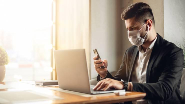 banquier devant son ordinateur portant un masque