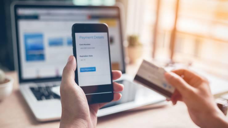 Homme utilisant sa banque en ligne sur smartphone et ordinateur