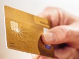 Personne présentant une carte bancaire dorée