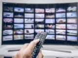 Une main presse les boutons de la télécommande d'une smart TV